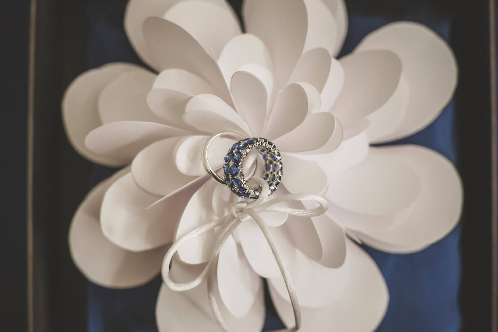 The wedding rings (Sabbadini, Milano): gold, sapphires and diamonds on the paper white flowers by Chicapui.