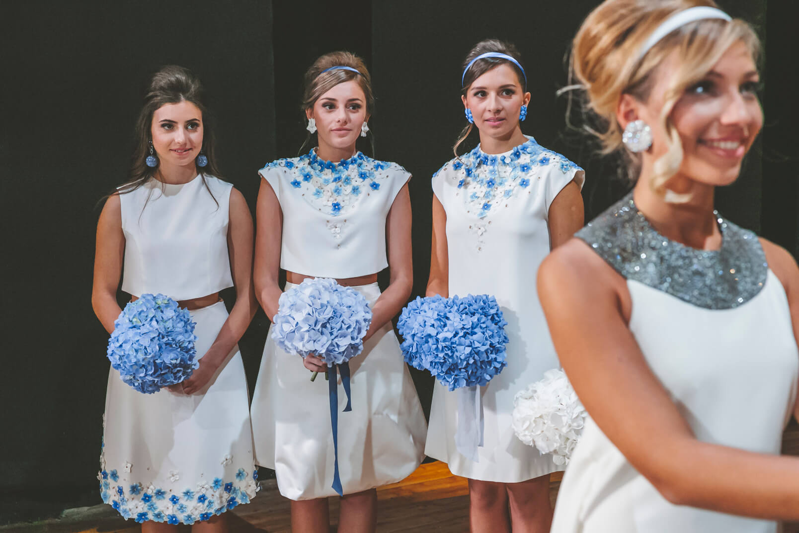 The three bridesmaids in their 60s mood dresses by Gretel Z. holding blue bouquets just before the exchange of the rings.