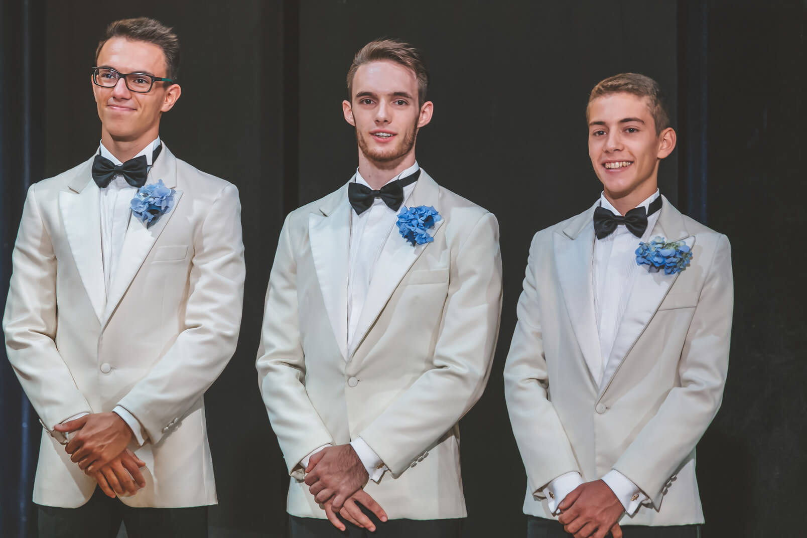 Bestmen's tuxedos (white jacket, black pants) and the blue buttonholes made with hortensia flowers.
