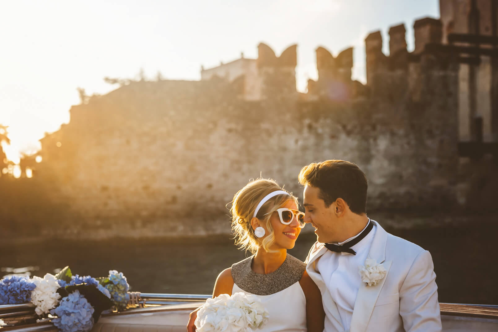 The bride and groom gazing. Amazing backlight at the sunset. 1960s mood glasses.