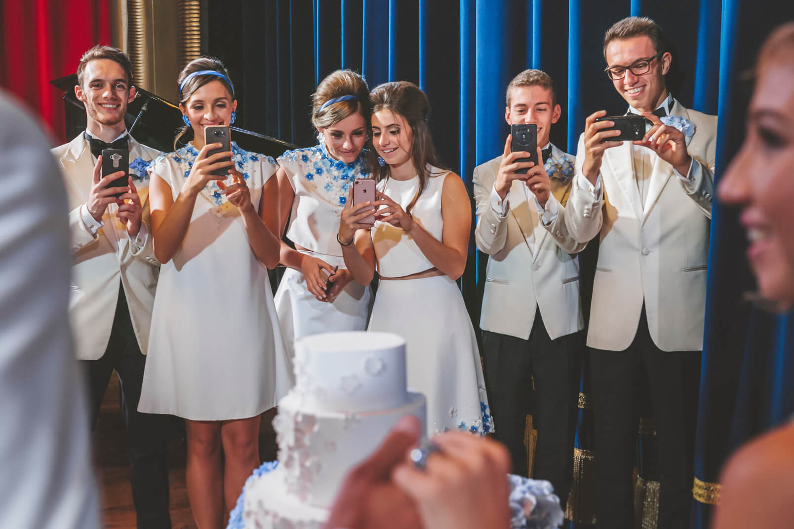 Bridesmaids and bestmen taking photos to the bride and groom using their phones.