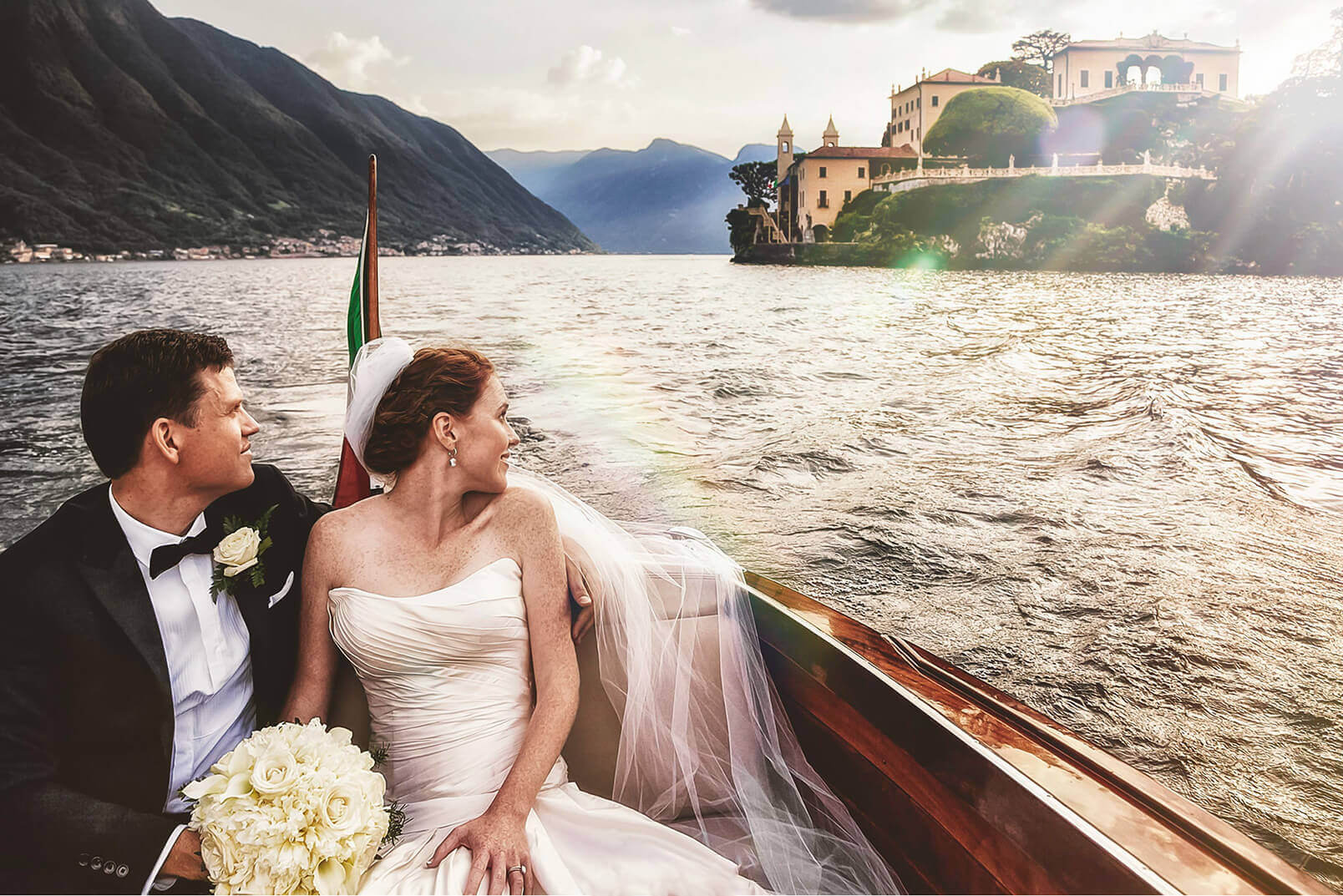 A couple looking at Villa del Balbianello during the taxi boat ride after their wedding.